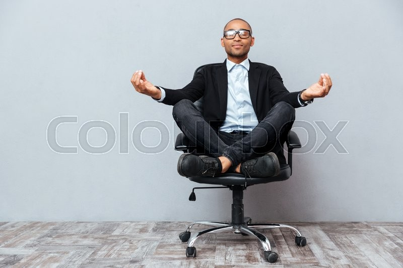 Relaxed handsome african young man sitting and meditating on office chair, stock photo