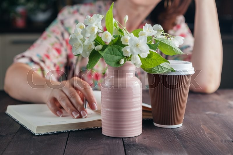 Woman dreams with coffee and flowers. Freelance concept, stock photo