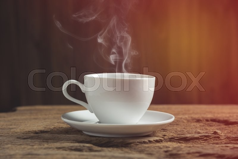 White coffee cup with smoke on wooden table, stock photo