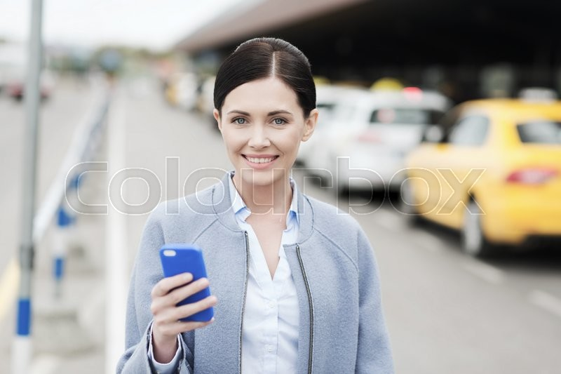 Travel, business trip, people and tourism concept - smiling young woman with smartphone over taxi station or city street, stock photo