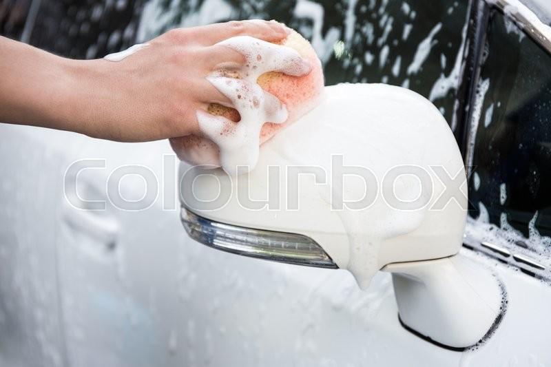 Car wash - male hand washing car mirror with sponge, stock photo