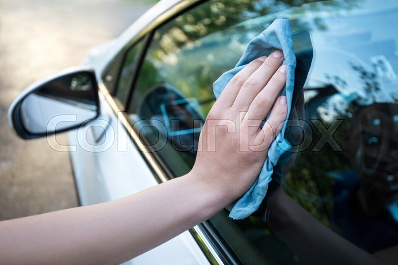 Male hand cleaning car window with blue microfiber cloth, stock photo