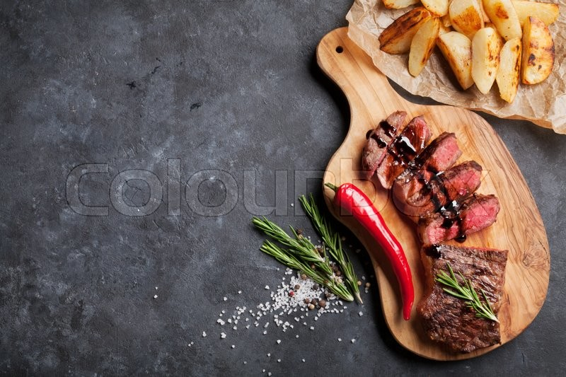 Grilled sliced beef steak on cutting board over stone table. Top view with copy space, stock photo