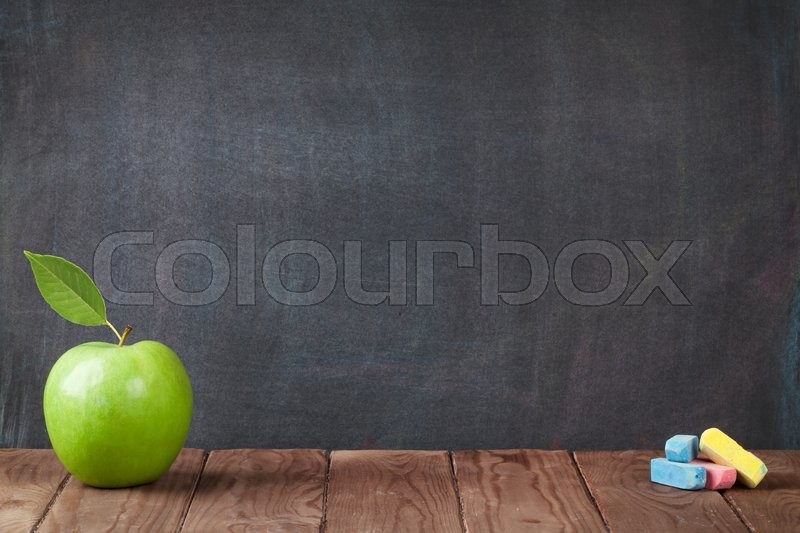 Apple fruit and chalks on classroom table in front of blackboard. View with copy space, stock photo
