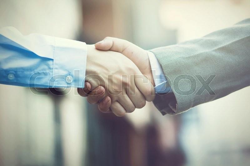 Business handshake. Two businessman shaking hands (Vintage tone), stock photo