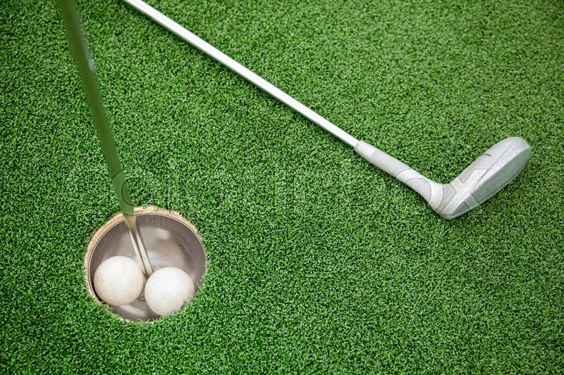 Putting golf club on green grass with golf ball in the hole - top view, stock photo