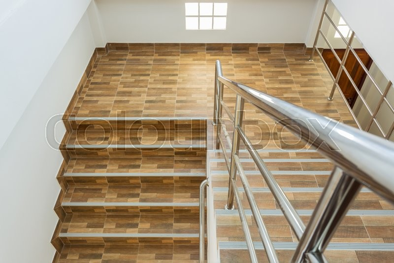 Staircase in residential house with stainless steel banister, ceramic floor tiles wood pattern, stock photo