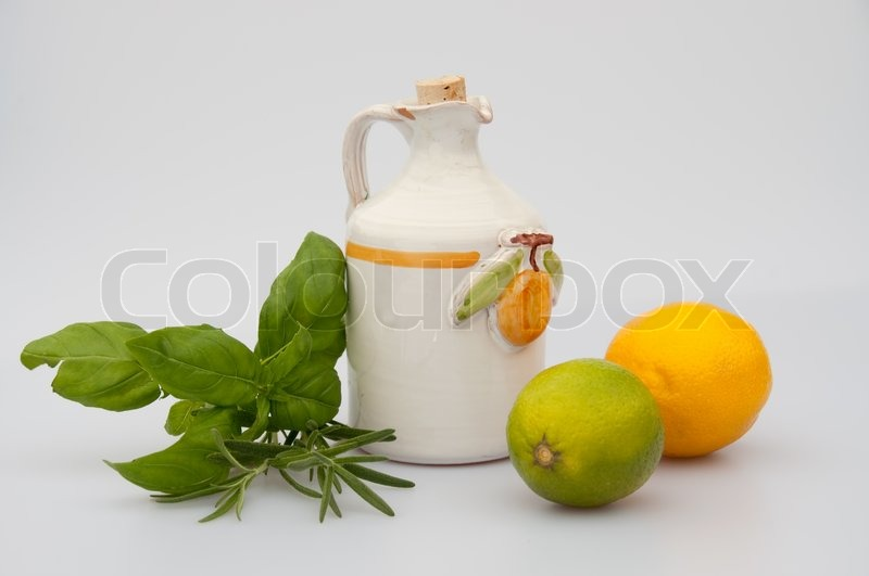 ... image of 'A lemon olive oil jug and lemon, lime and herbs. isolated
