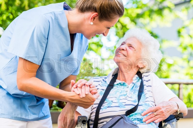Nurse holding hand of senior woman in pension home, stock photo