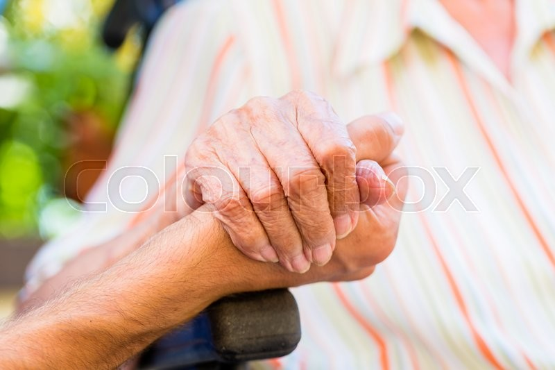 Nurse holding hand of senior woman in wheel chair, stock photo