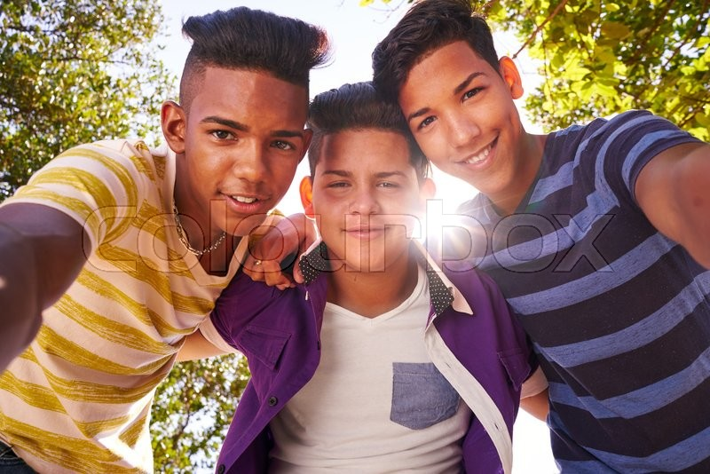 Youth culture, young people, group of male friends, multi-ethnic teens outdoors, teenagers together in park. Portrait of happy boys smiling, kids looking at camera. Slow motion, stock photo