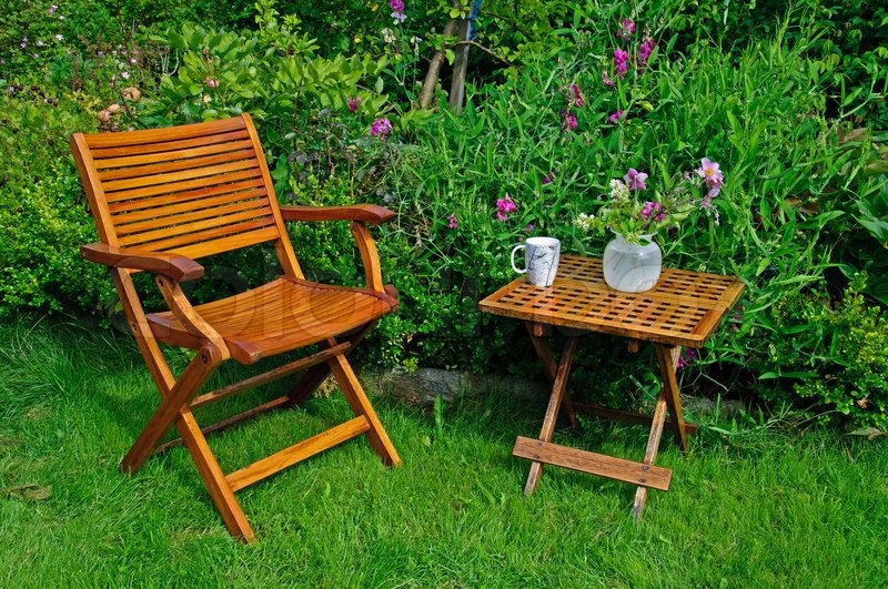 A Hardwood Garden Chair And Table Cup Of Coffe And A Vase