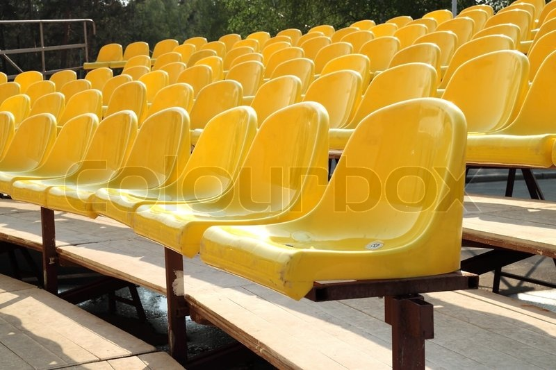 Empty Rows Of Yellow Plastic Chairs On Wooden Scaffold
