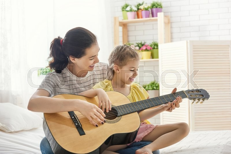 Happy family. Mother and daughter playing guitar together. Adult woman playing guitar for child girl, stock photo