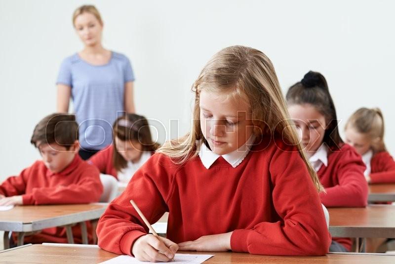Female Pupil At Desk Taking School Exam, stock photo