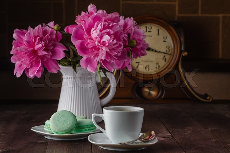 Cup of coffee and flowers (peonies) on daark wooden table, stock photo