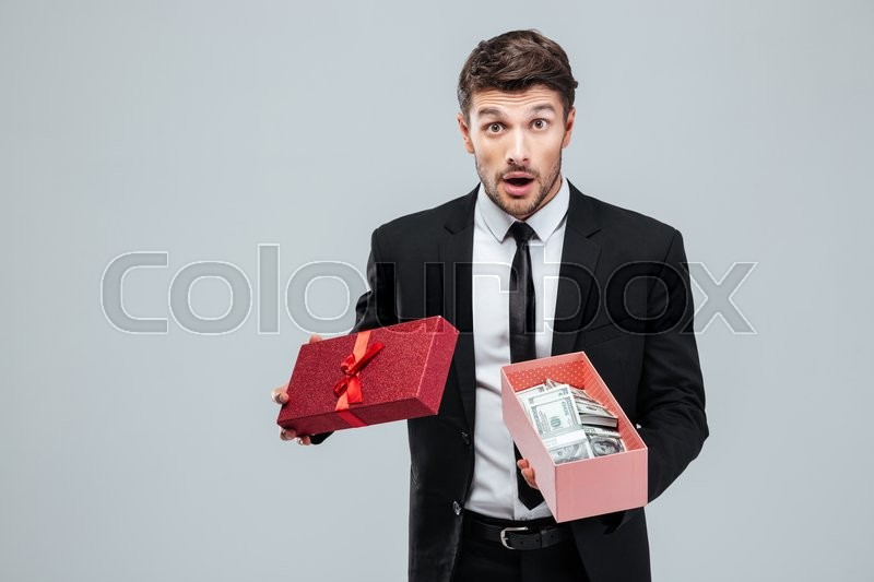 Surprised young businessman holding opened gift box with money over white background, stock photo