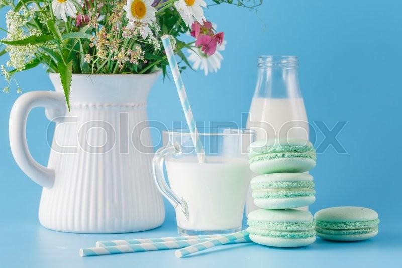 Fresh milk in glass mug and wildflowers with macaroons, stock photo