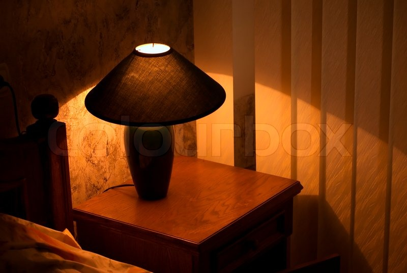 Cozy lamp on a night stand near a bed (shining in the darkness) | Stock  Photo | Colourbox
