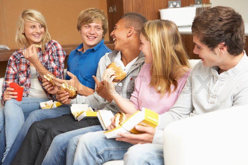 teenager freunden sitzen auf dem sofa zu hause essen fast food stockfoto colourbox. Black Bedroom Furniture Sets. Home Design Ideas