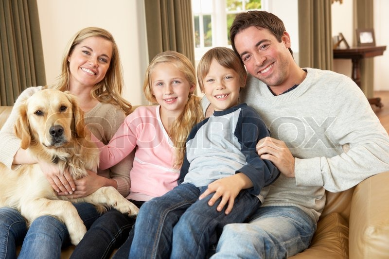 Happy young family sitting on sofa holding a dog, stock photo