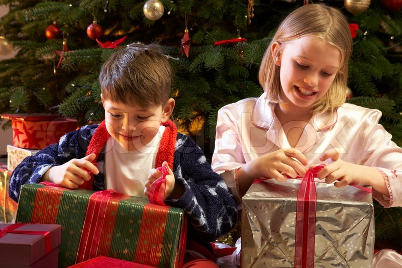 children opening christmas present in front of tree stock photo colourbox