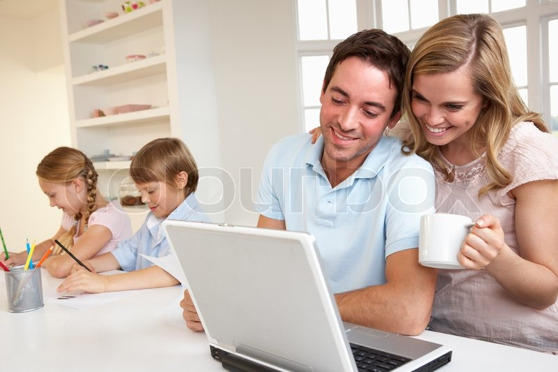 Stock image of 'Happy young family looking and reading a laptop computer'