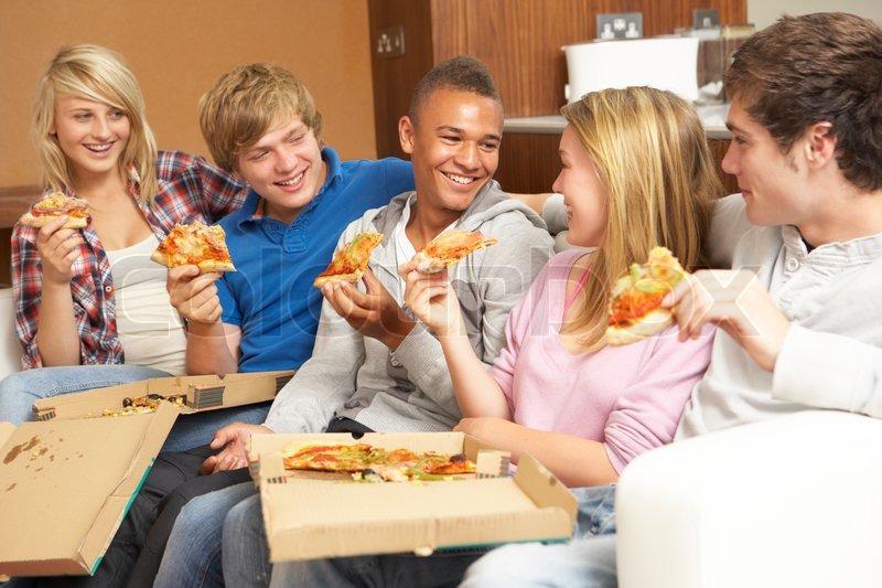 group of teenage freunde sitzen auf sofa zu hause essen pizza stockfoto colourbox. Black Bedroom Furniture Sets. Home Design Ideas