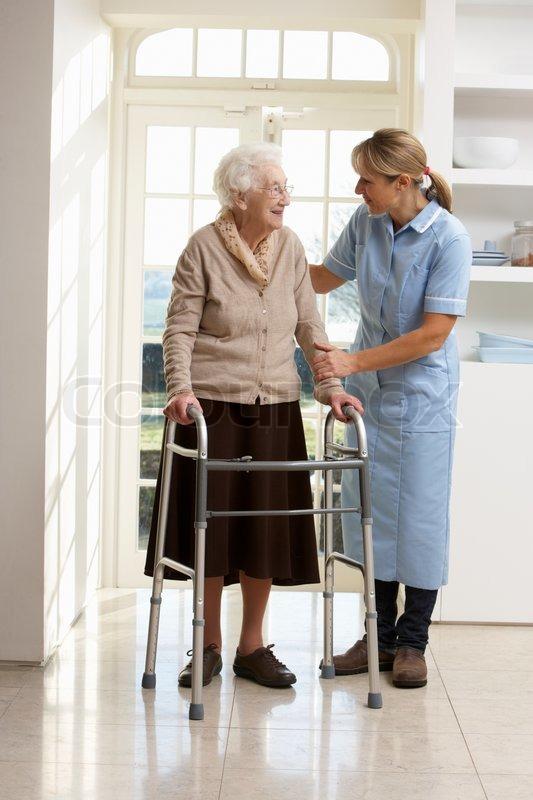 Carer helping elderly senior woman using walking frame for Aide soignante en maison de retraite