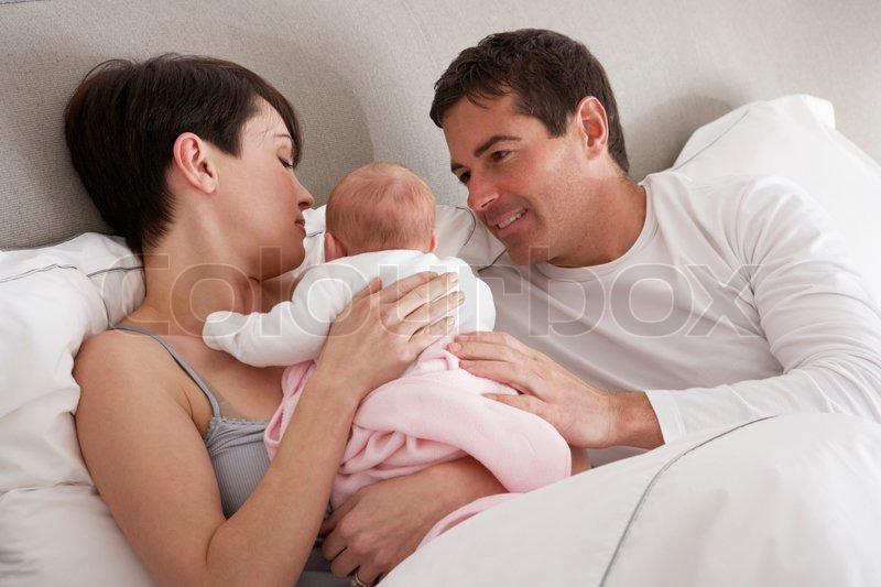 eltern kuscheln neugeborene baby zu hause im bett stockfoto colourbox. Black Bedroom Furniture Sets. Home Design Ideas