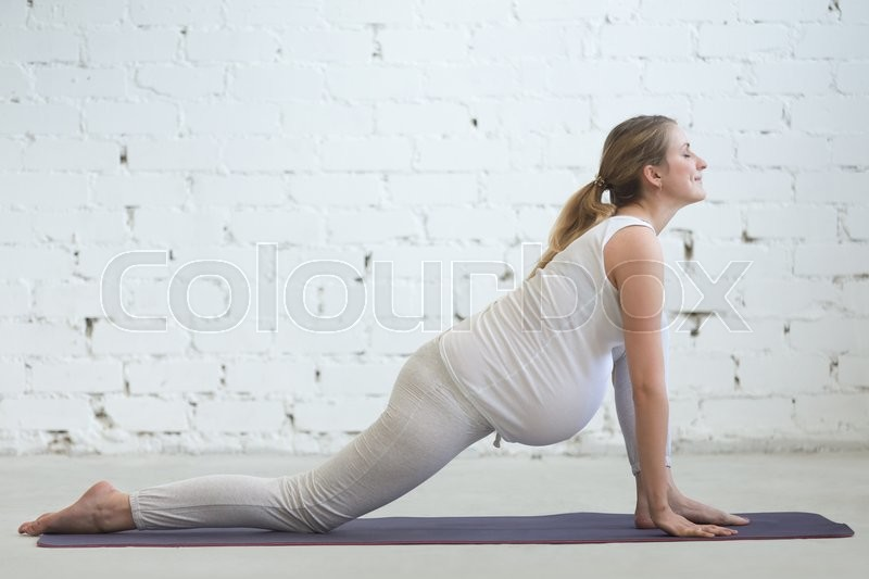 Pregnancy Yoga and Fitness. Young pregnant yoga model working out in loft room with white walls. Pregnant fitness person practicing yoga exercises at home. Prenatal Lizard (dragon yin pose) posture, stock photo