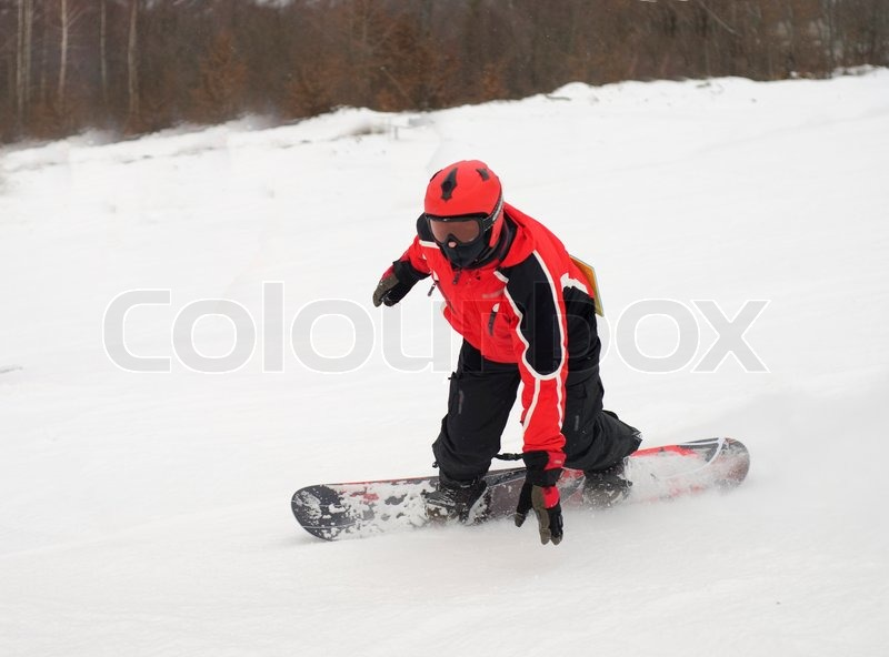 Stock image of 'Man on snowboard skiing down on mountain. It is snowing'