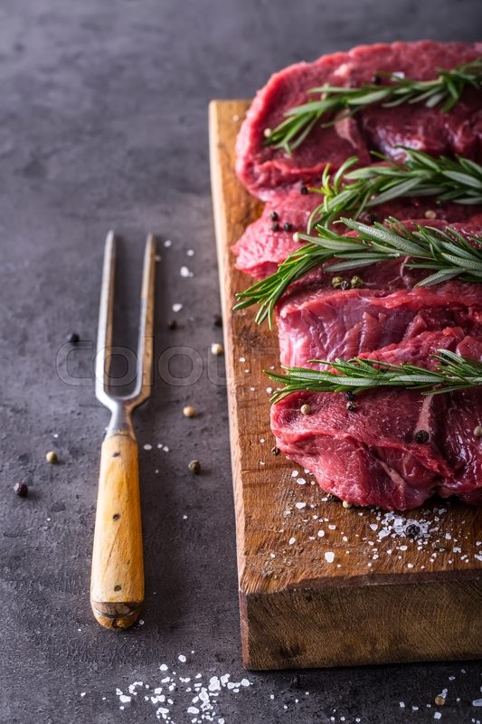 Steak. Raw beef steak. Fresh raw Sirloin beef steak sliced or whole ready for BBQ or grill. Herb - Rosemary decoration, stock photo