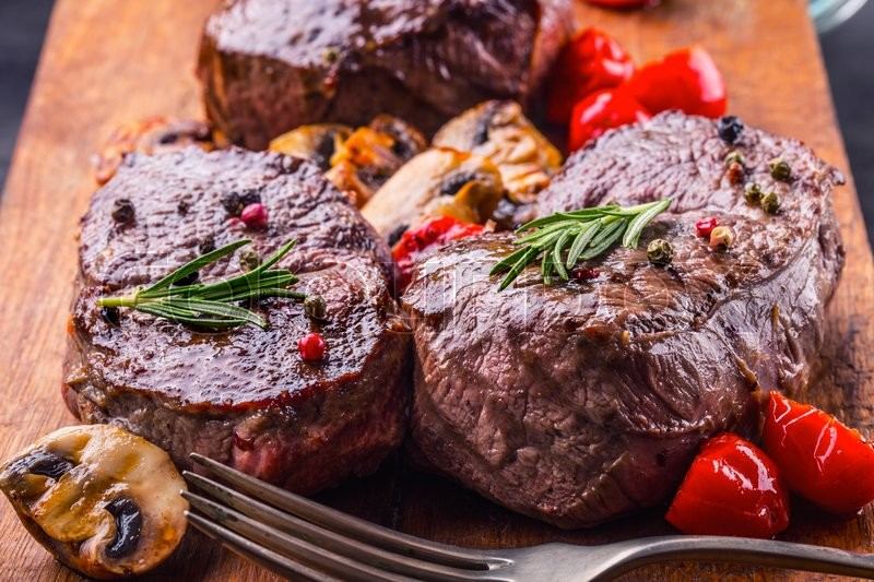 Grill beef steak. Portions thick beef juicy sirloin steaks on grill teflon pan or old wooden board, stock photo