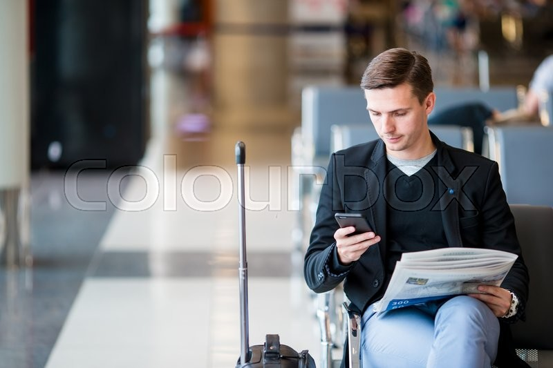 Passenger in an airport lounge waiting for flight aircraft. Young man with cellphone in airport waiting for landing, stock photo