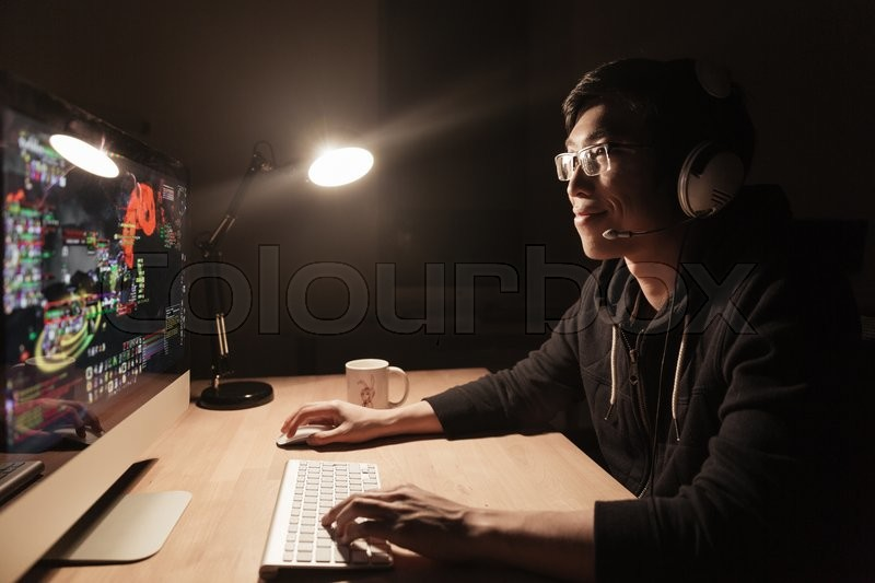 Happy handsome asian male gamer playing computer game at the table in dark room, stock photo