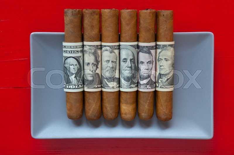 Gray ceramic dish and luxury Cuban cigars with US dollar banknotes on over red background, rectangle dish, stock photo
