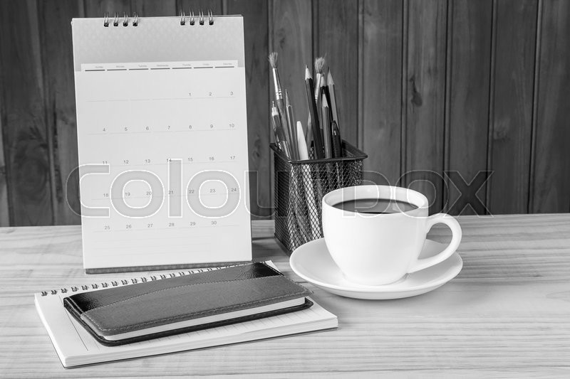 Black and white note book,coffee cup,and stack of book with calendar on wooden table background. Business concept, stock photo