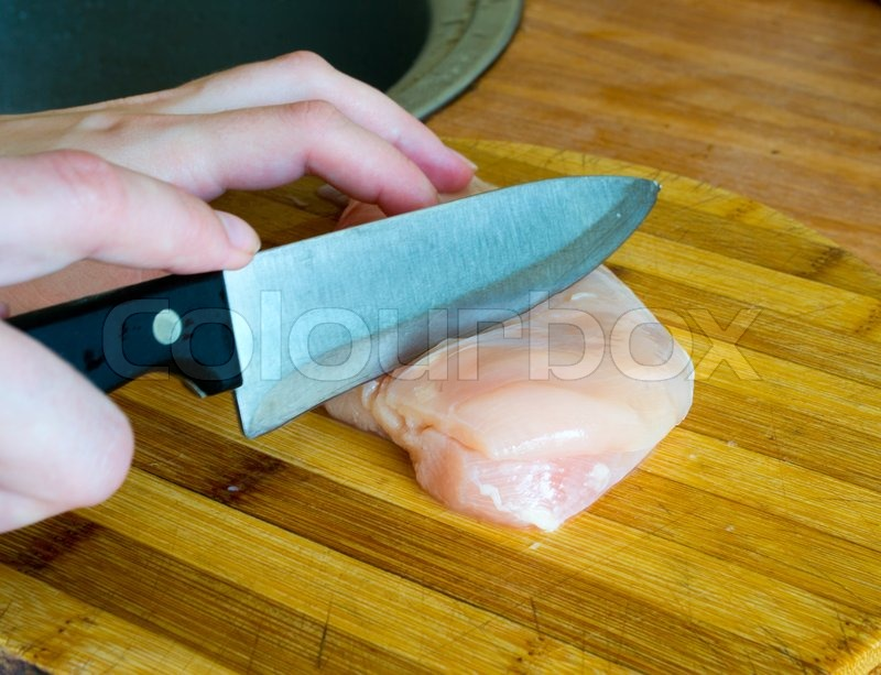 Hand cut meat with a knife | Stock Photo | Colourbox