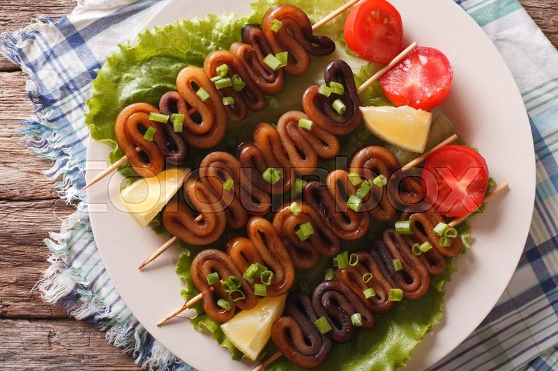 Kebab From Calamari On Skewers With Vegetables A Plate Horizontal View Above