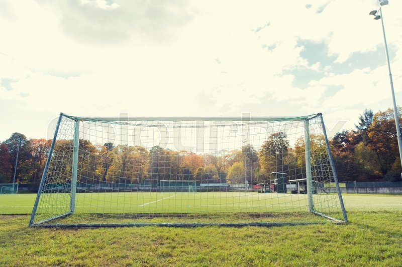 Sport and equipment concept - football goal on field, stock photo