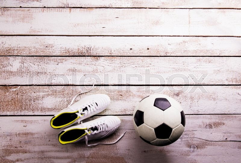 Soccer ball, cleats against wooden floor, studio shot on white background. Flat lay, copy space, stock photo