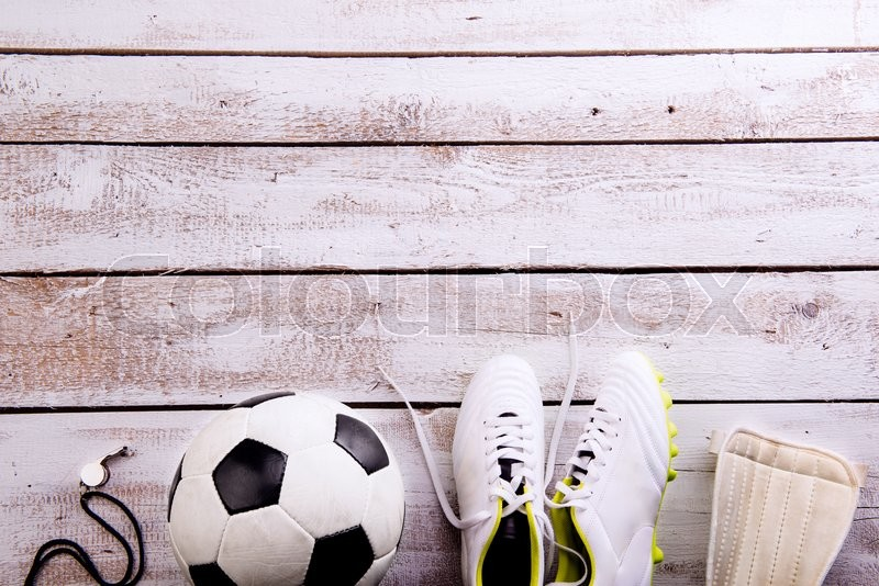 Soccer ball, cleats, protectors and whistle against wooden floor, studio shot on white background. Flat lay, copy space, stock photo