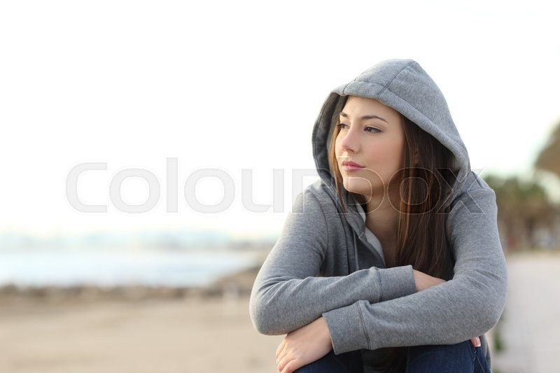 Portrait of a longing pensive teenager sitting on the beach looking away at the horizon in the morning, stock photo