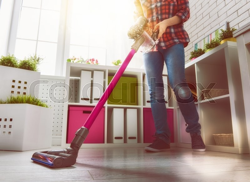 Woman makes cleaning the house. Woman vacuums the floor, stock photo