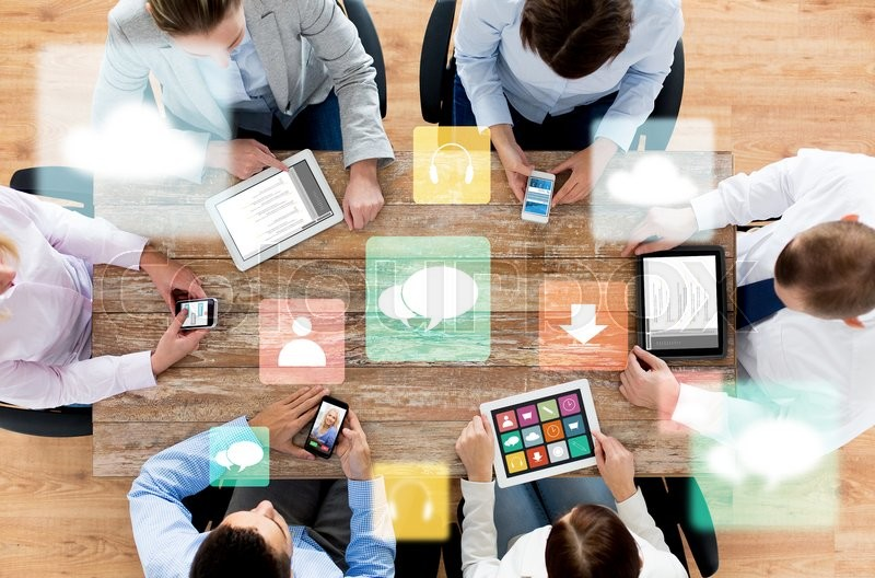 Business, people, technology, media and team work concept - close up of creative team with smartphones and tablet pc computers sitting at table in office, stock photo