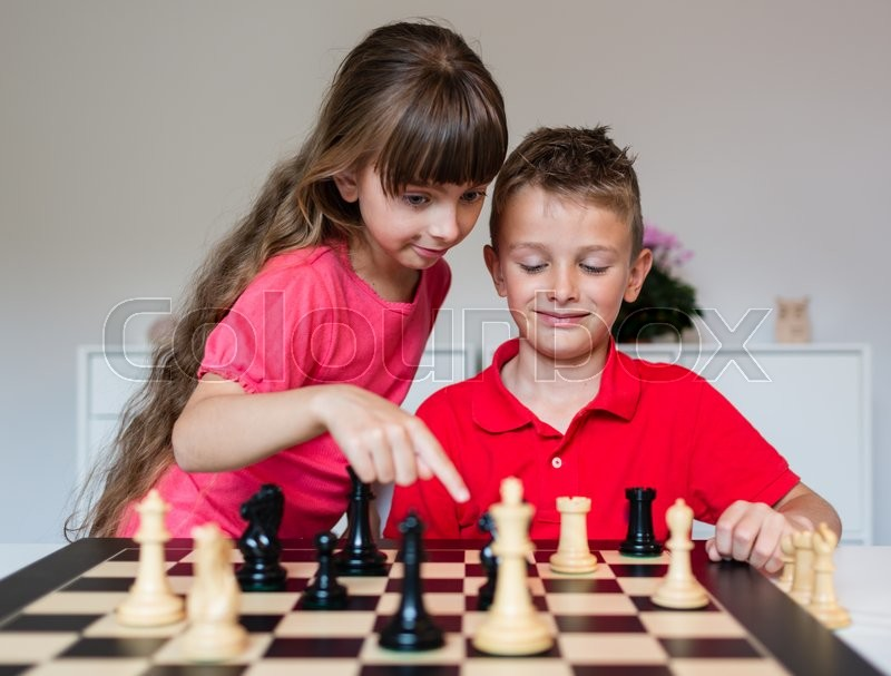 Girl helping boy while playing a game of chess on large chess board, stock photo