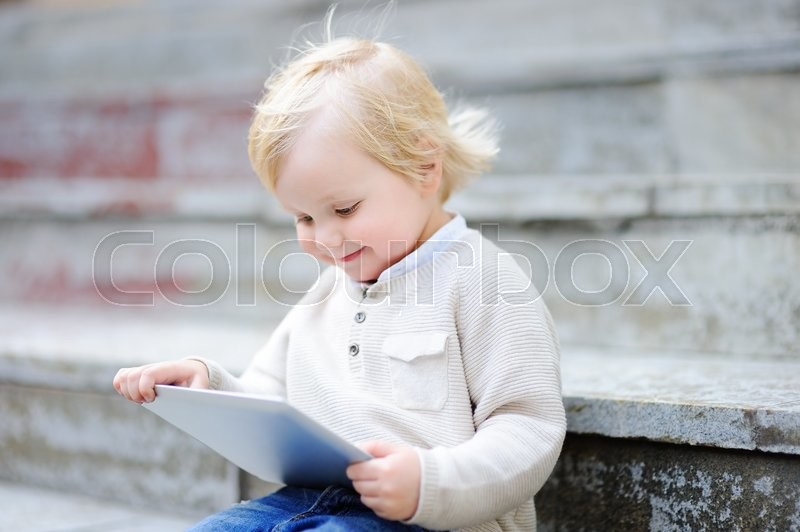 5c904f787ccc Cute blonde toddler boy playing with a ...