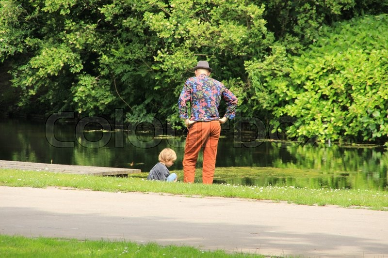 The father and his son discuter their problems along the pond in the park in the summer in the city Rotterdam, stock photo