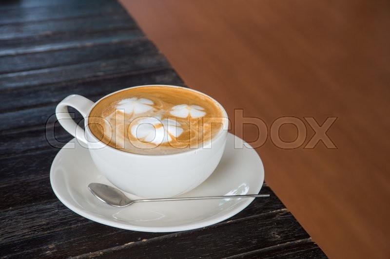 A cup of coffee with flower pattern in a white cup on wooden background, stock photo